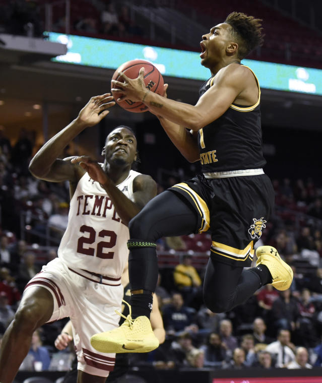 Wichita State's Tyson Etienne (1) drives to the basket as Temple's De'Vondre Perry (22) defends during the first half of an NCAA college basketball game Wednesday, Jan. 15, 2020, in Philadelphia. (AP Photo/Michael Perez)
