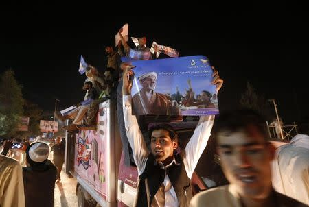 Supporter of Afghan presidential candidate Ashraf Ghani holds a poster as he celebrates in the street after the Independent Election Commission announced preliminary results in Kabul