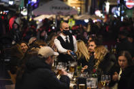 FILE - In this Wednesday, Nov. 4, 2020 file photo, a waiter wears a face mask as people eat and drink outside restaurants in Soho, in London. British Prime Minister Boris Johnson is expected to confirm Monday June 14, 2021, that the next planned relaxation of coronavirus restrictions in England will be delayed as a result of the spread of the delta variant first identified in India. (AP Photo/Alberto Pezzali, File)