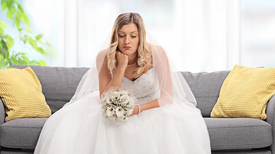 Upset bride sits on couch in her wedding dress