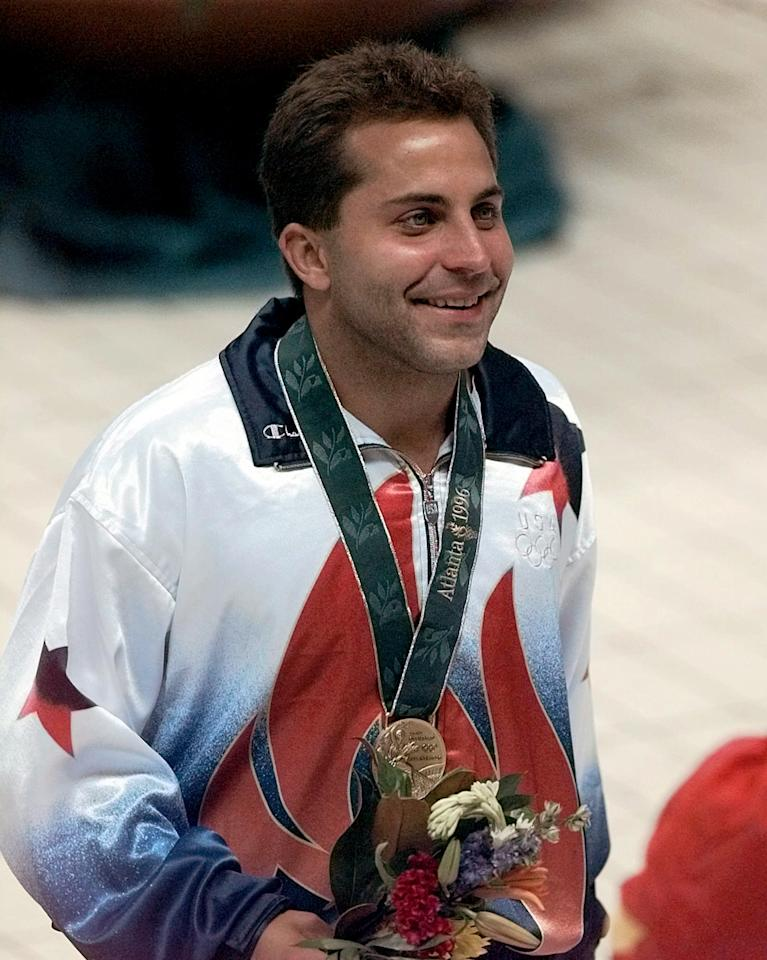 This July 29, 1996 file photo Mark Lenzi, of Bloomington, Indiana, winner of the bronze medal smiling after medal ceremony for the Olympic men's 3-meter springboard competition at Georgia Tech in Atlanta. A former Olympic diving champion, Lenzi has died. He was 43. Lenzi's alma mater, Indiana University, made the announcement Monday, April 9, 2012. Lenzi's hometown newspaper, The Free Lance-Star in Fredricksburg, Virginia, said Lenzi had been hospitalized for two weeks after suffering fainting spells. His mother, Ellie, told the newspaper her son's blood pressure was too low. (AP Photo/Amy Sancetta, File)