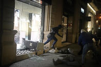 A person carrying goods runs from a smashed shop window during a protest condemning the arrest of rap singer Pablo Hasél in Barcelona, Spain, Saturday, Feb. 20, 2021. A fifth night of peaceful protests to denounce the imprisonment of a Spanish rap artist once more devolved into clashes between police and fringe group members who set up street barricades and smashed storefront windows in Barcelona. (AP Photo/Joan Mateu)