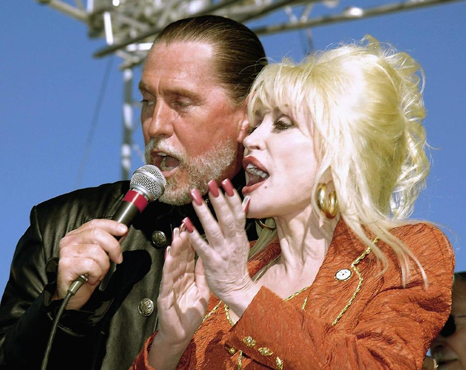 Dolly Parton shares the microphone with her brother, Randy, during a celebration marking the groundbreaking for the Carolina Crossroads Music & Entertainment Center, Friday, Nov. 11, 2005, in Roanoke Rapids, N.C. Randy Parton, plans to operate the project, which officials hope will be the first of a number of similar operations in the region.