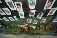 A makeshift memorial bears photos of some of the missing people that hangs from a fence, near the site of an oceanfront condo building that partially collapsed in Surfside, Fla., Friday, June 25, 2021. (AP Photo/Gerald Herbert)