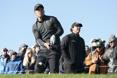 February 10, 2019; Pebble Beach, CA, USA; Paul Casey (left) hits his tee shot in front of Phil Mickelson (right) on the ninth hole during the final round of the AT&T Pebble Beach Pro-Am golf tournament at Pebble Beach Golf Links. Mandatory Credit: Kyle Terada-USA TODAY Sports