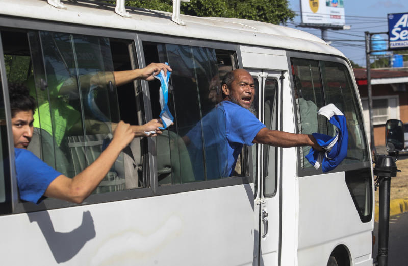 Alex Vanegas, right, and other prisoners who who had been imprisoned by the government of President Daniel Ortega for protesting against the regime, wave Nicaraguan flags aboard a prison bus, after being released, in Managua, Nicaragua, Wednesday, Feb. 27, 2019. Ortega's government has released dozens of people arrested in a last year's crackdown on street protests, just hours before talks between the government and opponents are scheduled to begin. (AP Photo/Alfredo Zuniga)