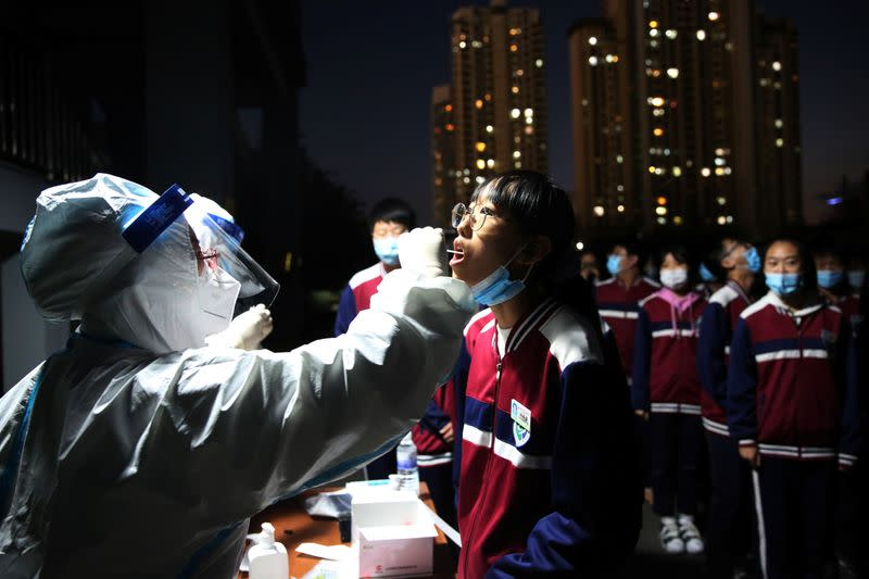 Medical worker collects a swab from a student for nucleic acid testing in Qingdao