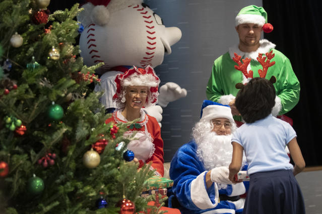 New York Mets outfielder Brandon Nimmo, center, dressed as Santa, his wife Chelsea Bradley, left, as Mrs. Claus and infielder J.D. Davis dressed as an Elf hand out gifts to local children during the team's annual Kids Holiday Party, Wednesday, Dec. 4, 2019, in New York. (AP Photo/Mary Altaffer)