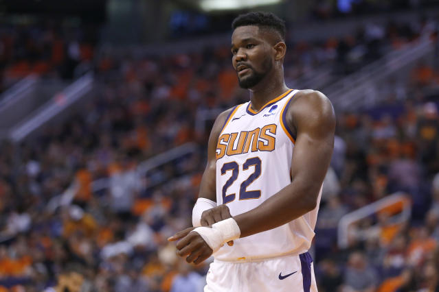 """Though losing <a class=""""link rapid-noclick-resp"""" href=""""/nba/players/5958/"""" data-ylk=""""slk:Deandre Ayton"""">Deandre Ayton</a> will be difficult for the <a class=""""link rapid-noclick-resp"""" href=""""/nba/teams/phoenix/"""" data-ylk=""""slk:Suns"""">Suns</a>, <a class=""""link rapid-noclick-resp"""" href=""""/nba/players/5473/"""" data-ylk=""""slk:Devin Booker"""">Devin Booker</a> thinks the suspension can actually bring the team together. (AP/Rick Scuteri)"""