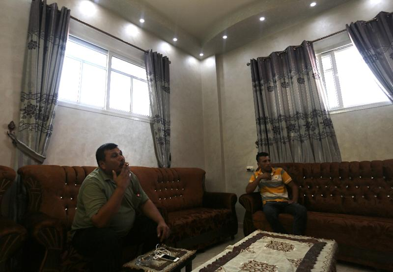 Palestinian Atef al-Zaza (left) sits on October 26, 2015 at his family's newly built house in Gaza City (AFP Photo/Mahmud Hams)