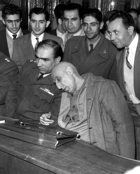 Ex-Iran prime minister Mohammad Mossadegh (R) rested his head on his lawyer's shoulder during his trial in a military court in 1953