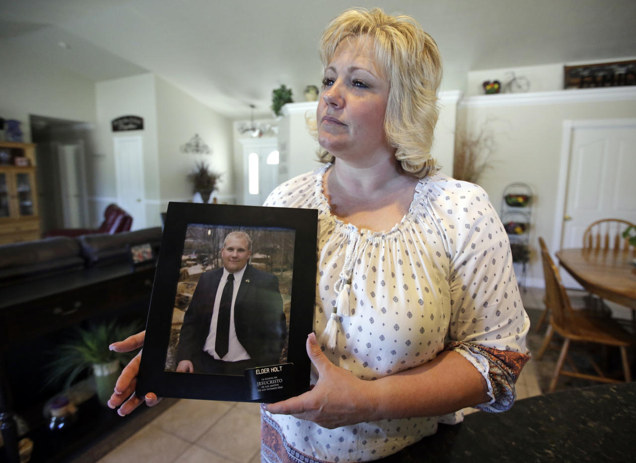 "FILE - In this July 13, 2016 file photo, Laurie Holt holds a photograph of her son Josh Holt at her home, in Riverton, Utah. Josh Holt has been released from a jail in Venezuela after spending nearly two years behind bars on weapons charges. Utah Sen. Orrin Hatch said on Twitter Saturday, May 26, 2018, that Joshua Holt had been released. President Donald Trump tweeted that it was ""good news,"" adding that Holt ""should be landing in D.C. this evening and be in the White House, with his family, at about 7:00 P.M."" (AP Photo/Rick Bowmer, File)"
