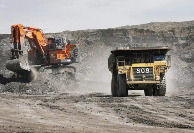 A haul truck carrying a full load drives away from a mining shovel at the Albian Sands oilsands mine near Fort McMurray, Alta. (Jeff McIntosh/The Canadian Press - image credit)