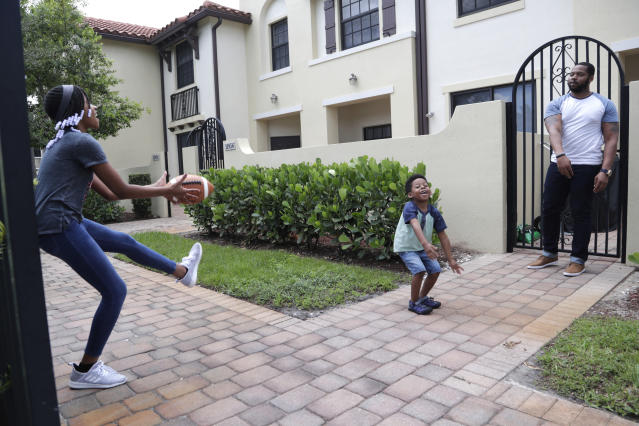 In this Tuesday, June 16, 2020 photo, D.J. Boldin, right, throws a football with his children Madison, 10, left, and Dallas, 4, center, outside of their home in Miramar, Fla. Boldin is the football coach at Pahokee High School, a predominantly black school located alongside Lake Okeechobee in Florida. Recent events have given Boldin an opportunity to use his position to prepare his players for the challenges they will face when they leave the bubble that is their small town. (AP Photo/Lynne Sladky)