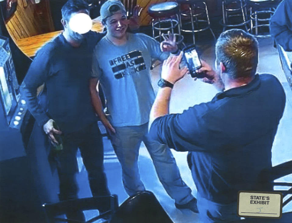 """In this image from video provided by the Kenosha County District Attorney, Kyle Rittenhouse poses for a photo at Pudgy's Pub in Mount Pleasant, Wis., on Jan. 5, 2021, the day he was arraigned on charges related to the killing of two people at an August protest in Kenosha. Prosecutors presented this photo and others as evidence of Rittenhouse consorting with white supremacists, citing the use of the """"OK"""" sign, which has been co-opted as a sign of """"white power."""" Rittenhouse's attorney said he is not and has never been a member of a white supremacist group. Rittenhouse's shirt and the face of the man posing with him were redacted by the source. (Courtesy of Kenosha County District Attorney via AP)"""