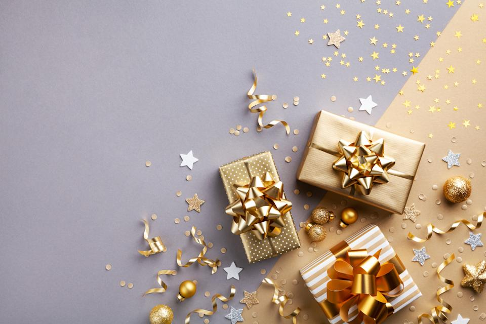 Golden gift or present boxes with golden bows and confetti top view. Christmas background. Flat lay style.