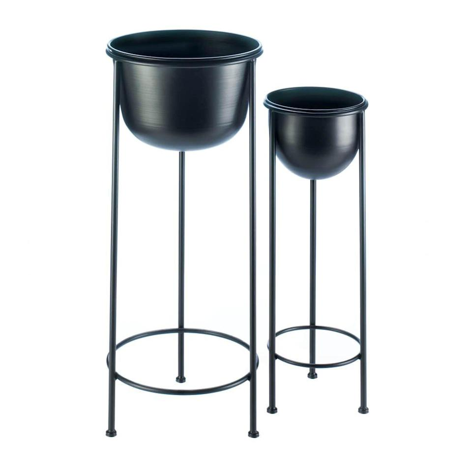 """<p><strong>Ebern Designs</strong></p><p>wayfair.com</p><p><strong>$59.99</strong></p><p><a href=""""https://go.redirectingat.com?id=74968X1596630&url=https%3A%2F%2Fwww.wayfair.com%2Ffurniture%2Fpdp%2Febern-designs-tiara-bucket-2-piece-nesting-plant-stand-set-zngz4705.html&sref=https%3A%2F%2Fwww.popularmechanics.com%2Fhome%2Fg36421088%2Fbest-plant-stands%2F"""" rel=""""nofollow noopener"""" target=""""_blank"""" data-ylk=""""slk:Shop Now"""" class=""""link rapid-noclick-resp"""">Shop Now</a></p><p>These plant stands work well with a range of decor, and can be used indoors or out. The removable planters are metal, as are the sturdy stands, which have a black weather-resistant powder-coated finish. The large stand is roughly 2.5 feet high and can hold a 12-inch-wide pot, and its smaller counterpart is about 2 feet tall and can accommodate an 8-inch-wide pot. The set is also a great value, priced at $60 at the time of this writing.</p>"""