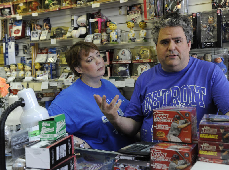 In this photo made Oct. 18, 2012, Todd, right, and Ula Nelkin, dressed in Detroit Lions t-shirts, talk about their autographed Barry Sanders card in their shop in Houston. Desperate for a baby, the couple is trying to raise money for in vitro fertilization by auctioning the rare football card. (AP Photo/Pat Sullivan)
