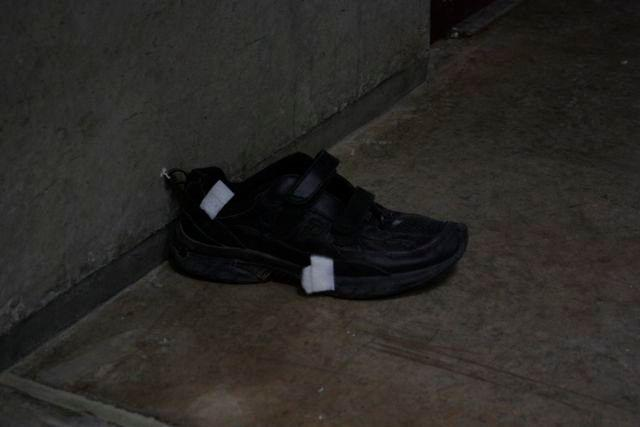 A shoe from a detainee left on the now-empty cell block.