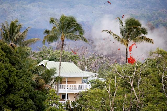 <p>Smoke and lava erupt from a fissure near a home on the outskirts of Pahoa during ongoing eruptions of the Kilauea Volcano in Hawaii, May 14, 2018. (Photo: Terray Sylvester/Reuters) </p>
