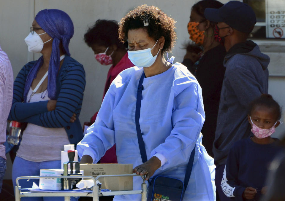 A healthcare worker pushes her trolley past people queuing to be tested for COVID-19 at the Livingstone Hospital in Port Elizabeth, South Africa, Friday, Nov. 13, 2020. The Eastern Cape Province is seeing a surge in cases of coronavirus and has recorded the highest number of COVID-19-related deaths in the country. (AP Photo/Theo Jeptha)
