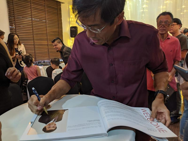 SDP leader Chee Soon Juan signs the party's coffee-table book containing its manifesto on 28 September, 2019. (PHOTO: Wong Casandra/Yahoo News Singapore)