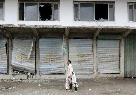Residents walk past damaged shops after a suicide car bomb attack on a government security building in Kabul, Afghanistan