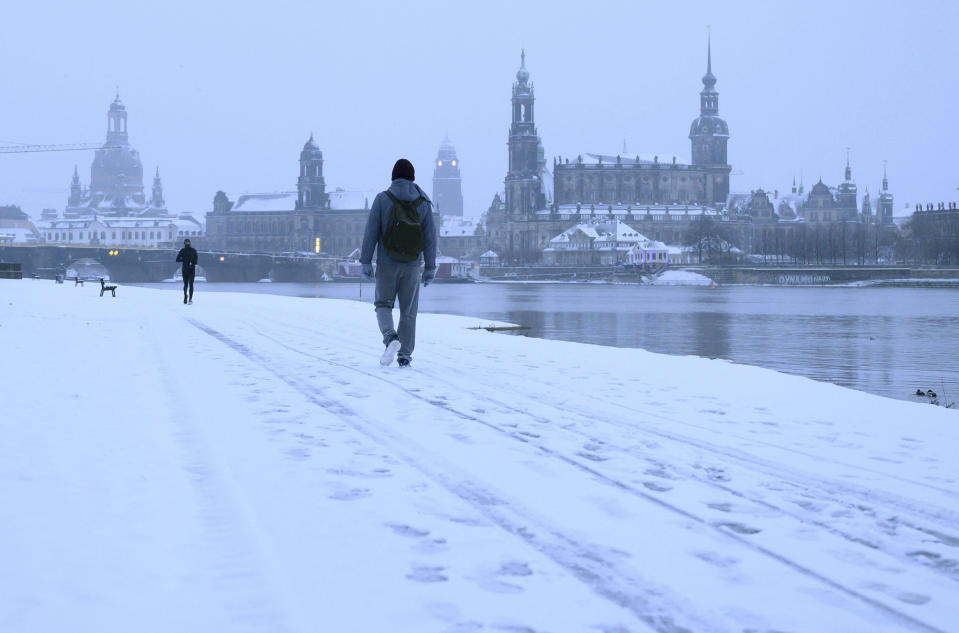 Passers-by walk through the snow in the morning on the banks of the Elbe river against the backdrop of the old town in Dresden, Germany, Sunday, Feb. 7, 2021. (Sebastian Kahnert/dpa via AP)