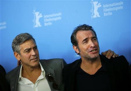 """Director and actor George Clooney and cast member Jean Dujardin (R) attend a photocall to promote the movie """"The Monuments Men"""" during the 64th Berlinale International Film Festival in Berlin February 8, 2014. REUTERS/Thomas Peter"""