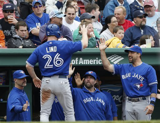 Toronto Blue Jays' Adam Lind (26) is greeted at the dugout after scoring on a single by teammate Colby Rasmus in the fourth inning of a baseball game against the Boston Red Sox in Boston, Saturday, May 11, 2013. (AP Photo/Michael Dwyer)