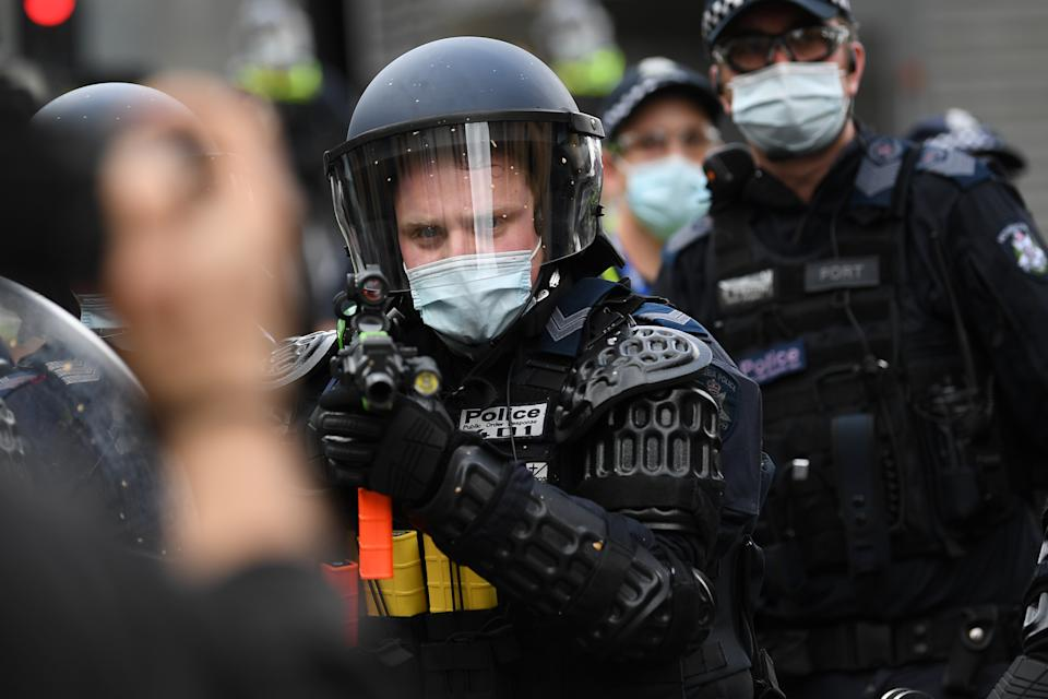 Police are seen in riot gear during an anti-lockdown protest on Saturday as an officer aims his weapon at demonstrators. Source: AAP
