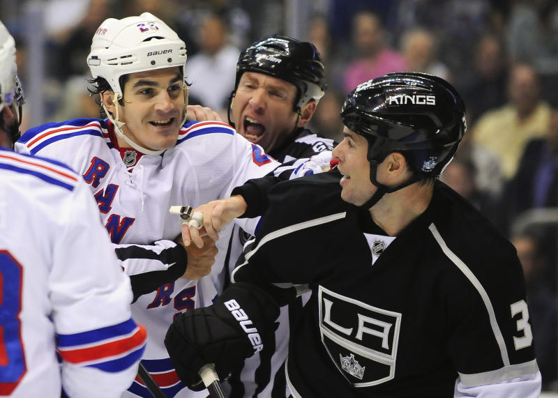 New York Rangers center Brian Boyle, left and Los Angeles Kings defenseman Willie Mitchell, right, mix it up during the first period of an NHL hockey game, Monday, Oct. 7, 2013, in Los Angeles. (AP Photo/Gus Ruelas)