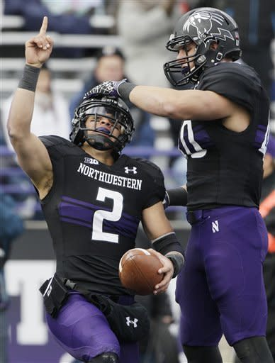 Northwestern quarterback Kain Colter (2) points as he celebrates with slotback Dan Vitale (40) after scoring a touchdown during the first half of an NCAA college football game against Illinois in Evanston, Ill., Saturday, Nov. 24, 2012. (AP Photo/Nam Y. Huh)