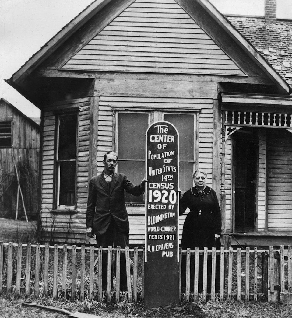 """<p>An Indiana couple, Mr. and Mrs. John Herrin, pose outside their farmhouse in Bloomington, Indiana. Their home was declared """"the center of the population,"""" according to the 1920 U.S. census.</p>"""