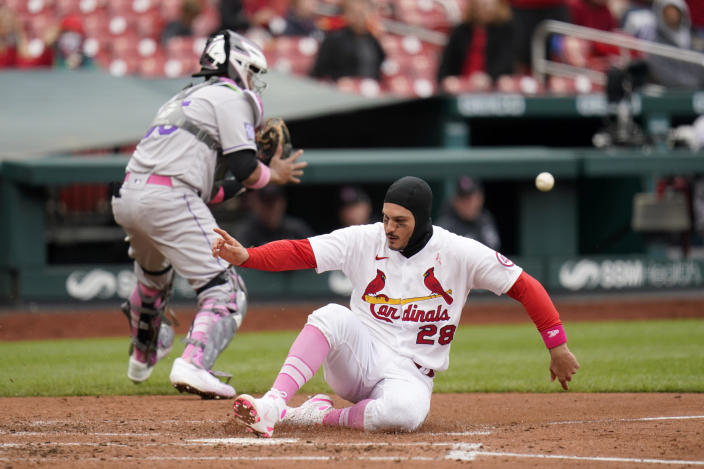 St. Louis Cardinals' Nolan Arenado (28) scores as Colorado Rockies catcher Elias Diaz handles the throw during the fourth inning of a baseball game Sunday, May 9, 2021, in St. Louis. (AP Photo/Jeff Roberson)