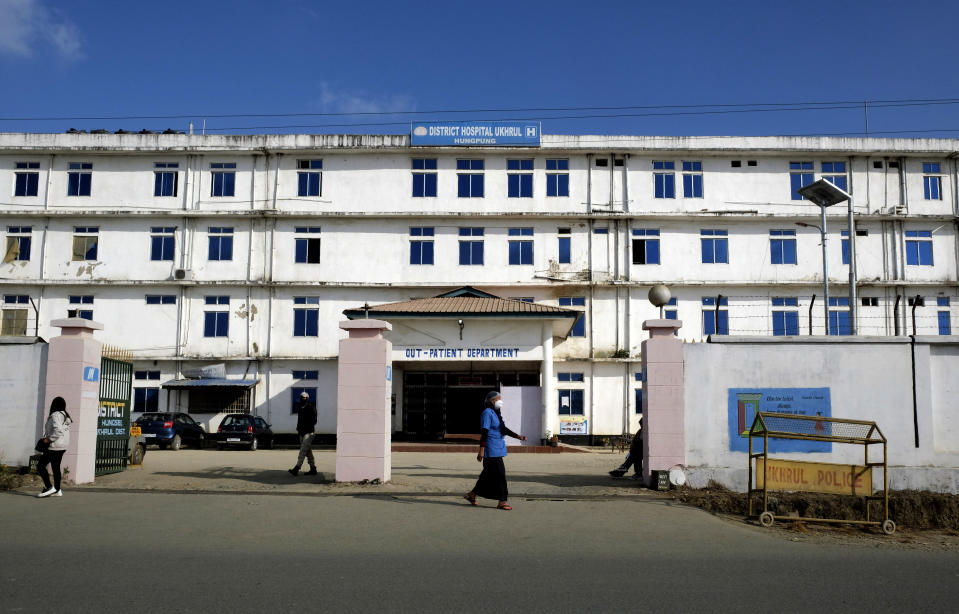 A hospital employee walks past the gate of the District Hospital in Ukhrul, in the northeastern Indian state of Manipur, Friday, Jan. 15, 2021. This is the only government-run medical facility in the district that caters to a population of 180,000. The country's COVID-19 vaccination campaign that began Saturday is also being carried out here. (AP Photo/Yirmiyan Arthur)