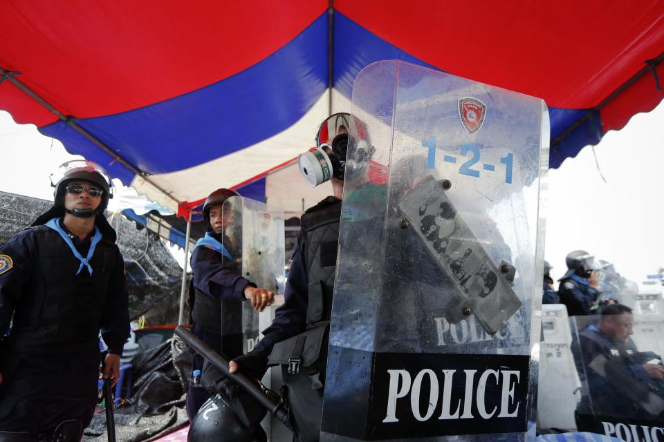 Policemen stand under a tent in the Thai national colours as they enter an encampment of anti-government protesters during clashes near the Government House in Bangkok February 18, 2014. A Thai police officer was killed and dozens of police and anti-government protesters were wounded in gun battles and clashes in Bangkok on Tuesday, officials and witnesses said. REUTERS/Damir Sagolj (THAILAND - Tags: SOCIETY CIVIL UNREST POLITICS)