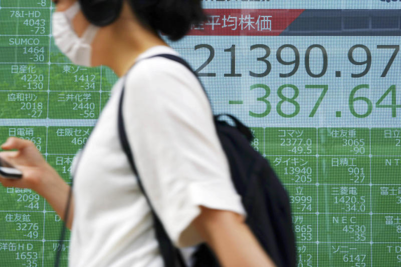 A woman walks past an electronic stock board showing Japan's Nikkei 225 index at a securities firm in Tokyo Thursday, Oct. 3, 2019. Asian stocks fell for a fourth day Thursday as weaker U.S. manufacturing and hiring data fueled jitters about the global economy. (AP Photo/Eugene Hoshiko)