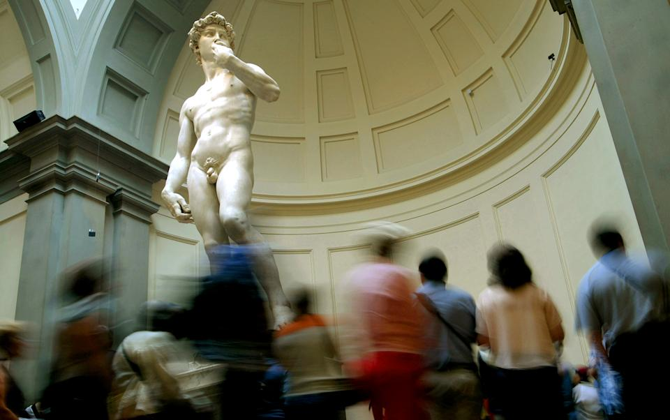 Visitors to the Accademia Museum stop to get a closer look at Michelangelo's statue of David in Florence September 8, 2004. 500 years to the day that the icon of Renaissance male beauty was unveiled to the people of Florence, his modern-day co-citizens on Wedndesday are kicking off a year of events to celebrate David in style. REUTERS/Max Rossi  DJM/ACM