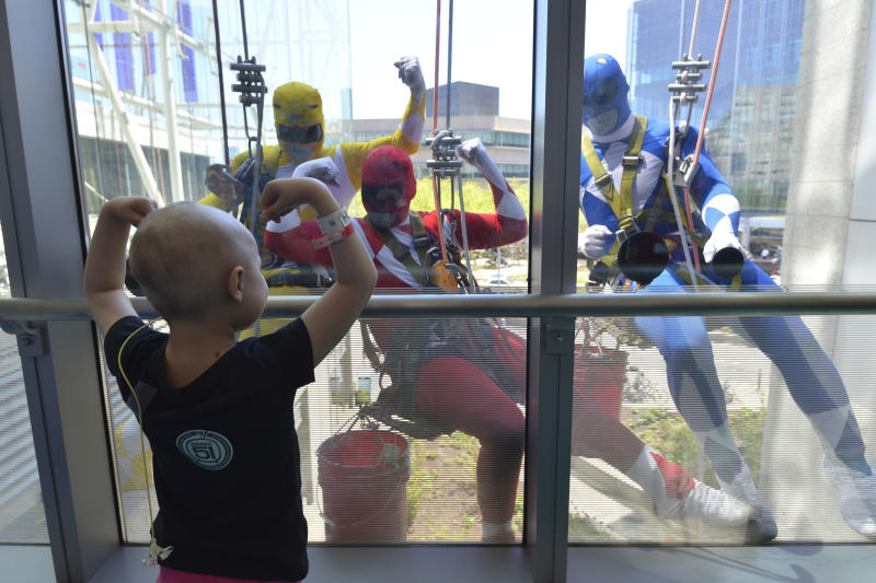 In this Tuesday, April 18, 2017 photo provided by Hal S. Edelson, a patient at the Children's Hospital of Philadelphia flexes her muscles for window washers dressed up as Power Rangers. The window washers with Jenkintown Building Services dress in costumes once a year to give the children, their parents and hospital staffers a thrill.  (Hal S. Edelson/HSE Photography via AP)