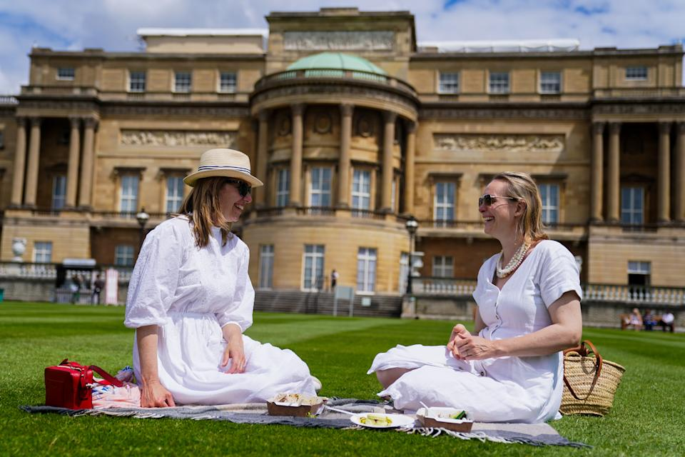 Alex Campbell (left), 38, and Lara Curry, 38 enjoy a picnic on the lawn during a preview of the Garden at Buckingham Palace, Queen Elizabeth II's official residence in London, which opens to members of the public on Friday. Visitors will be able to picnic in the garden and explore the open space for the first time. Picture date: Thursday July 8, 2021. (Photo by Kirsty O'Connor/PA Images via Getty Images)