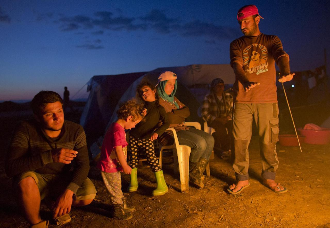 Refugees from Syria warm themselves as they sit around a fire at the informal camp in Idomeni, Greece, Sunday, May 22, 2016. Thousands of stranded refugees and migrants have camped in Idomeni for months after the border was closed. (AP Photo/Darko Bandic)