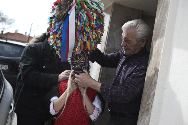 In this Monday March 11, 2019 photo, a grandfather helps a young bell wearer with the costume in the village of Sohos, northern Greece, to participate in a Clean Monday festival. Greek carnivals at this time of year can be modest but they showcase ancient rites and traditions as well as providing reminders to some bloody moments in the country's modern history. In northern Greece, two of the most celebrated carnival customs are found in the mountain town of Sochos, and in Naoussa. (AP Photo/Petros Giannakouris)