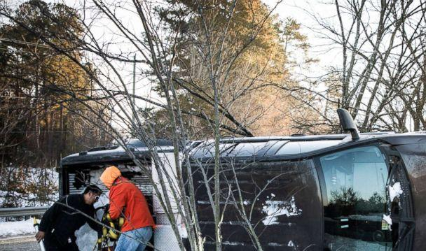 PHOTO: The driver, Alenjandro Rangel, right, and a man who assisted him, grab tools from the truck bed after the truck flipped after running over a patch of ice too quickly, Dec. 11, 2018, in Carrboro, N.C. (Julia Wall/The News & Observer via AP)