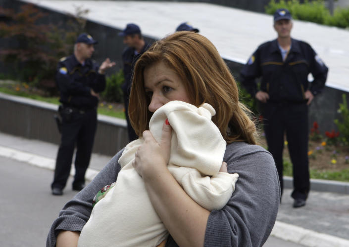 A Bosnian woman with her baby takes part in a protest in front of the Bosnian parliament building in Sarajevo, on Wednesday, June 5, 2013. Dozens of people are blocking the entrance to Bosnia's Parliament demanding lawmakers to pass a new law on personal identification numbers after the old one came out of force in February, leaving all babies born since then without personal documents. Bosniak, Serb and Croat lawmakers can't agree about the territorial regions that would issue the numbers. The result is depriving newborns the ID numbers needed to get health insurance or a passport. (AP Photo/Amel Emric)