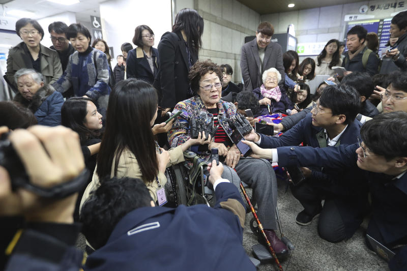 Former South Korean comfort woman Lee Yong-soo, center, speaks before leaving the Seoul Central District Court in Seoul, South Korea, Wednesday, Nov. 13, 2019. A Seoul court on Wednesday began hearing a long-awaited civil case filed against the Japanese government by South Korean women who were forced to work in Japan's World War II military brothels. (AP Photo/Ahn Young-joon)