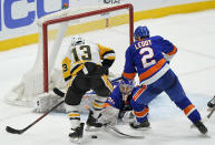 New York Islanders goaltender Ilya Sorokin (30) makes a save as Pittsburgh Penguins left wing Brandon Tanev (13) threatens with Islanders defenseman Nick Leddy (2) defending the crease during the third period of an NHL hockey game, Sunday, Feb. 28, 2021, in Uniondale, N.Y. (AP Photo/Kathy Willens)