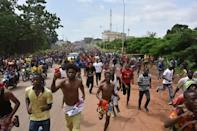 People in Conakry greet members of Guinea's armed forces on September 6, the day after the coup that toppled Alpha Conde (AFP/CELLOU BINANI)