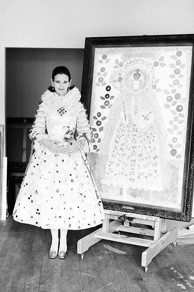 <p>Posing with one of her paintings wearing a dress designed by Adolfo to match the painting.</p>