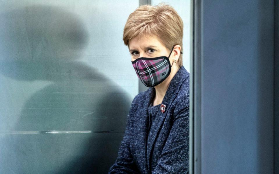 Nicola Sturgeon wearing a face mask arrives for the First Minister's Questions session at the Scottish Parliament - PA